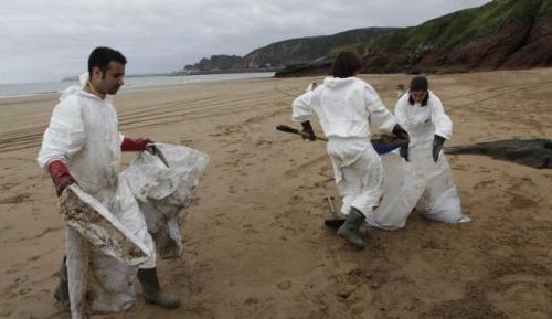 Trabajadores de HC, ayer, limpiando en la playa de Xivares. Ángel González