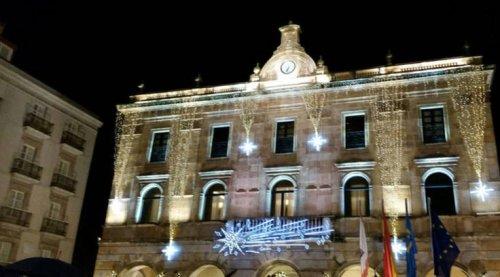 Bien iluminada ya, la devastada casa consistorial. No podía faltar la bandera napoleónica, o del IV Reich, abajo a la derecha... (Foto www.asturias24.es)